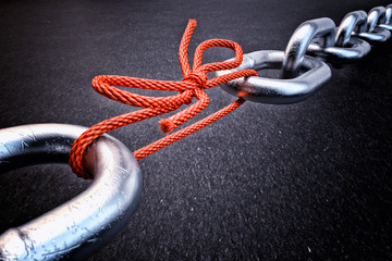 Weakest link, security break fix and strength concept, metallic chain connected by a red knotted rope on black background