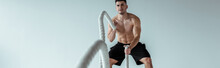 Selective Focus Of Sexy Muscular Bodybuilder With Bare Torso Exercising With Battle Rope On Grey Background, Panoramic Shot