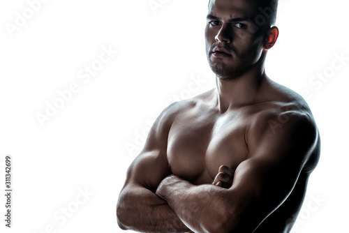 Fototapeta  sexy muscular bodybuilder with bare torso posing with crossed arms in shadow iso