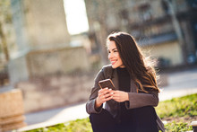 Attractive Young Woman Looking At Her Smart Phone And Smiling While Sitting