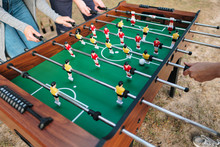 Friends Play Table Football Or Kicker Outdoors. Players And Fans Rejoice In The Victory.