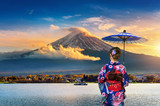 Asian woman wearing japanese traditional kimono at Fuji mountain. Sunset at Kawaguchiko lake in Japan.