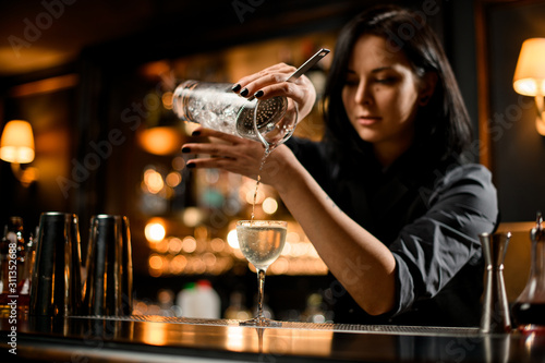 Professional bartender girl pouring a trasparent alcoholic drink from the measur Canvas Print