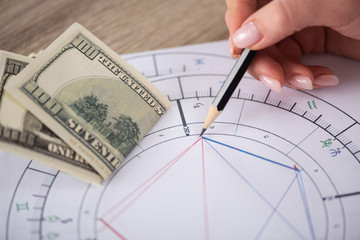 Cropped view of astrologer drawing natal chart beside dollar banknotes on table