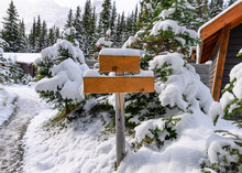 Snow Covered On Empty Wooden Signpost On Cottage