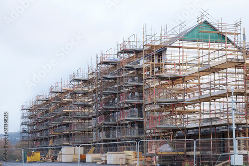 Fototapeta Building affordable homes with scaffolding safety by local construction council