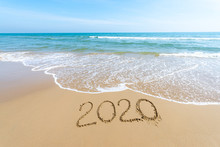 Text 2020 Happy New Year On The Beach With Waves And Clear Blue Sea. 2020 Numbers On The Coast. Hand Written Messages In Sand On A Beautiful Beach Background