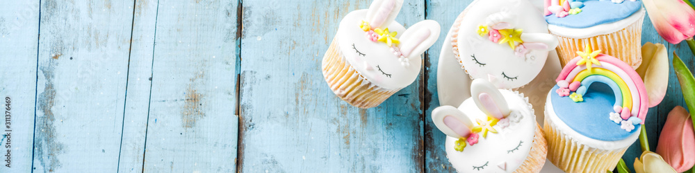 Fototapeta Easter holiday greeting card background. Cute homemade cupcakes with traditional Easter bunny, egg and springtime flowers decor. Happy easter concept. Copy space for your text