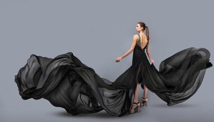beautiful young girl in flying black dress. Flowing fabric. Light black fabri...