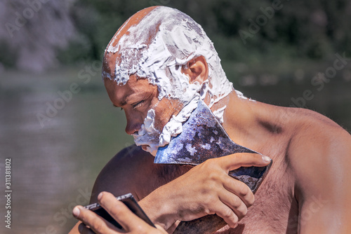 man shaves with an ax in nature Canvas Print