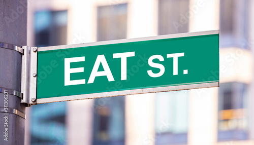 Eat street sign, street food concept, blur buildings background Wallpaper Mural