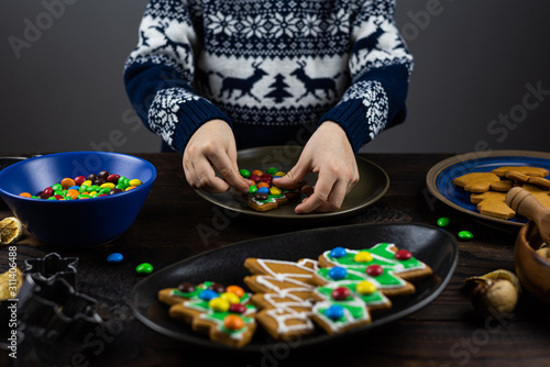 The child decorates with candys a gingerbread in the shape of a Christmas tree. Close up children's hands, lots of sweets on a wooden table.