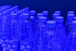 Leinwanddruck Bild - Bottles of clean drinking water on a blue background