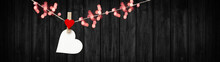 Happy Valentine's Day Background Banner Panorama - White Heart Hang On Wooden Clothes Pegs With Wooden Heart And Bokeh Lights On A String Isolated On Black Rustic Wooden Wall, With Space For Text