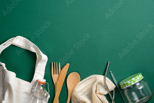 Photo  Eco friendly bamboo cutlery, glass jar, bottle, reusable canvas shopper bag and metal drinking straws on green background