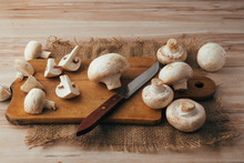 Slicing Mushrooms On A Wood Cutting Board. Whole And Cut Champignons.
