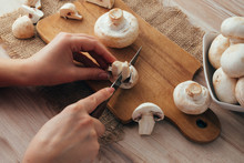 Champignon Mushrooms On A Wood Cutting Board. Woman Cook Slicing Food. Top Down View.