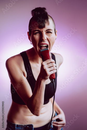 Fotografía  Young and attractive girl with shaved hair and punk style sings