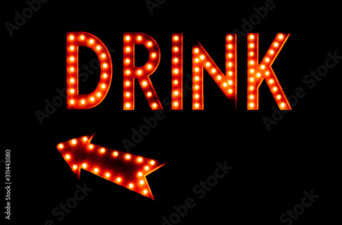 Fototapeta Illuminated vintage neon marquee drink sign with arrow against a black background at night. Drinks this way sign. obraz na płótnie
