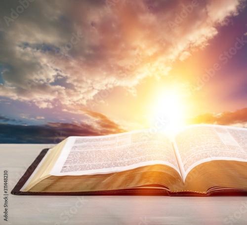 Fotografia  Holy Bible book on a sunset background