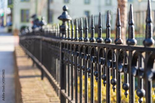 Vászonkép Black Iron Fence along a Small Town Main Street sidewalk.