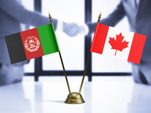 Canada And Afghanistan Mini Table Flags On White Wooden Desk. Diplomatic Background With Men Shaking Hands, International Relations And Agreements.