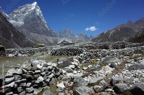 Old stone walls in Phulaji Kala (4344 m), Everest trek, View of Arakam Tse (6423 Fototapet