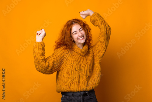 Fotografia Photo of ginger young woman, having fun and celebration with rised hands, over i