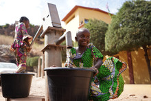 Two Colorful Dressed African Girls Fetching Water At The Borehole