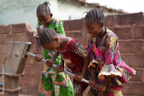 Three Smiling Little African Girls Busy Fetching Water At The Village Pump Fototapet