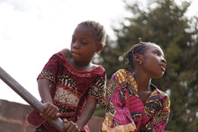 Two Little African Girls Making Efforts To Pump Water From The Public Borehole