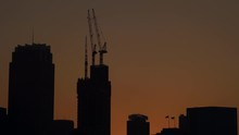 Sydney, Australia - Silhouette Of Tower Cranes And High Rise Buildings Under The Dark Sky With Two Flags Swaying In The Wind During Sunset - Wide Shot