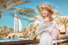 Cheerful Asian Tourist Girl With The Famous Burj Al Arab Hotel Building In Dubai. Tourism In United Arab Emirates