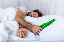 Drunk Man In The Bed And Sad Place And An Alcohol Bottle In His Hand. Young Man Lying In Bed Deadly Drunken Holding Near-empty Bottle Of Booze.