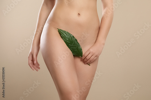 Woman with leaf showing smooth skin on beige background, closeup Canvas Print