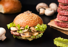 Sandwich With Meat And Mushrooms On A Wooden Board On A Black Background Next To The Ingredients