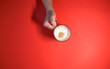 canvas print picture - Close-up of a man's hand holding a Cup of coffee, on a red background.  Concept of drinking coffee. Copy space. Top view.