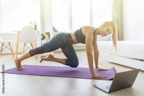Attractive sportswoman with laptop doing push ups at home. Obraz na płótnie