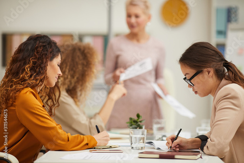 Vászonkép Businesswomen making notes while their middle-aged colleague demonstration her p