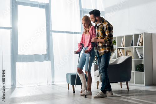bearded man looking at injured woman holding crutches at home Wallpaper Mural