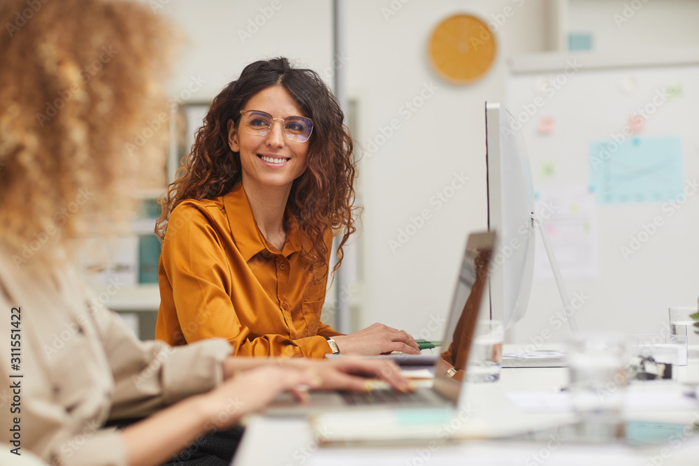 Fototapeta Two beautiful female colleagues interacting while working in office