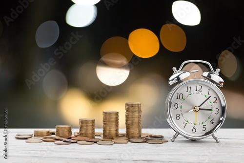 Fotografía Stack golden coins with alarm clock, Save  time money concept