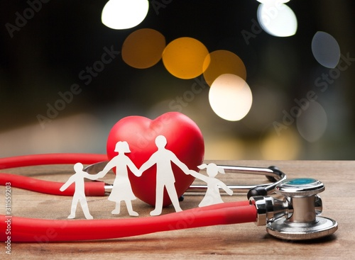 Fotografia  Family cut-out and stethoscope on wooden desk, Medical Insurance Concept