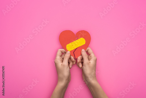 Cuadros en Lienzo  cropped view of holding broken paper heart with patch isolated on pink backgroun