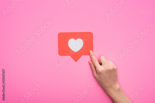 partial view of woman holding paper like sign isolated on pink - 311567657