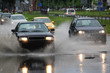 driving car on flooded road during flood caused by torrential rains. Cars float on water, flooding streets. Splash on the car. Flooded city road with a large puddle
