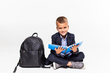 Primary Schoolboy Sitting On Floor And Reading Isolated On White Background