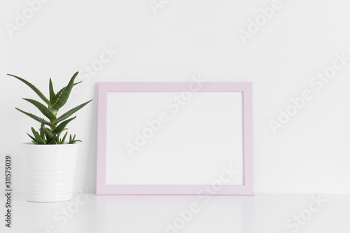 Fototapety, obrazy: Pink frame mockup with a aloe vera in a pot on a white table.Landscape orientation.