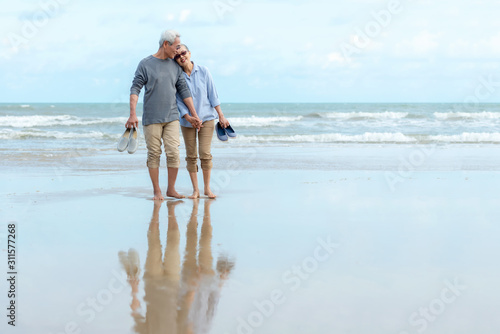 Lifestyle asian senior couple happy walking hug and relax on the beach Wallpaper Mural