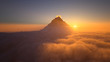 Leinwandbild Motiv Mountain peak above the clouds at sunset